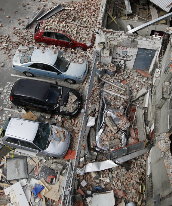 Cars lie under rubble in the central business district in Christchurch. Courtesy of Getty Images.