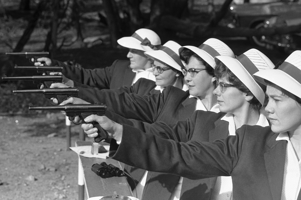 """Johannesburg housewives fire .22 pistols at a target during one of the weekly """"pistol parties"""" in the capital of jittery white supremacist South Africa, Aug. 30, 1963. These housewives belong to a pistol-packers' club of women aged 25 to 61, all top marksmen. They bring coffee and sandwiches for a mid-morning break during their practice on the range. It's all part of South Africa's defense build-up against attacks which the country's leaders say they expect from other African countries. (AP Photo/Dennis Lee Royle)."""