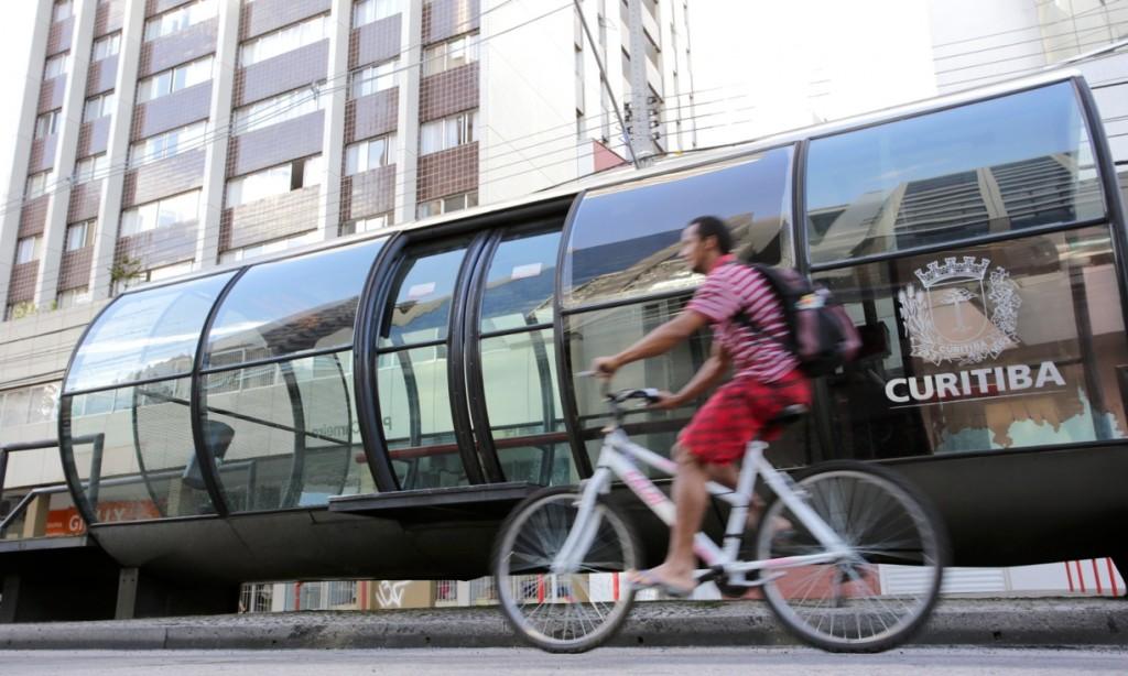 A cyclist passes a Bus Rapid Transit (BRT) stop in Curitiba, Brazil.